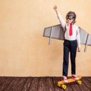 Success of young businessman with toy paper wings.